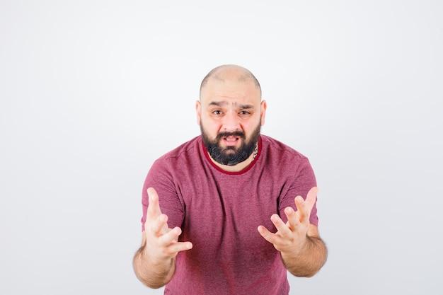 Jonge man steekt handen op agressieve manier op in roze t-shirt en ziet er nerveus uit. vooraanzicht.