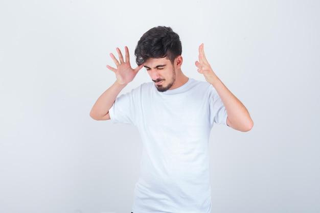 Jonge man steekt handen op agressieve manier op in t-shirt en kijkt geïrriteerd, vooraanzicht.