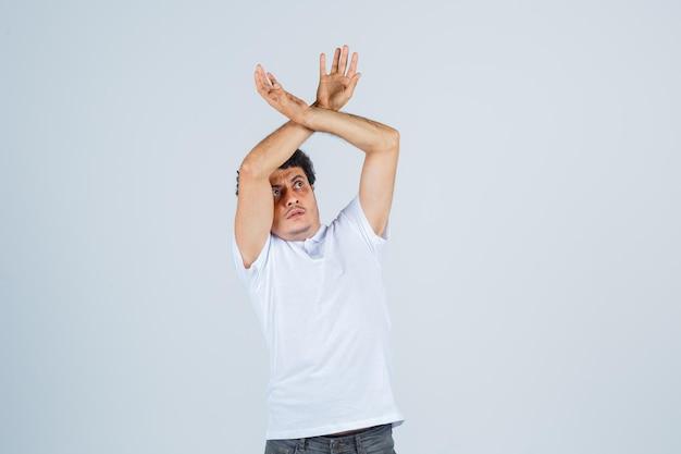 Jonge man steekt handen op om zichzelf te verdedigen in wit t-shirt, broek en ziet er bang uit. vooraanzicht.