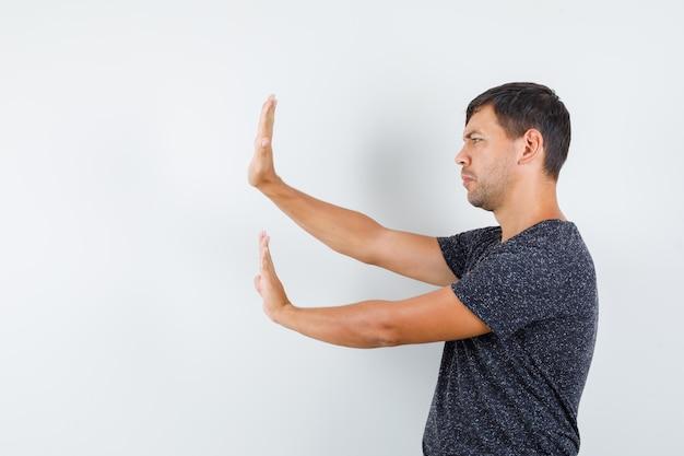 Jonge man steekt zijn handen preventief op in t-shirt en ziet er bang uit. .