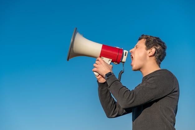 Jonge man stemt naar megafoonwaarschuwing van gevaarlijke gebeurtenis. kopieer ruimte