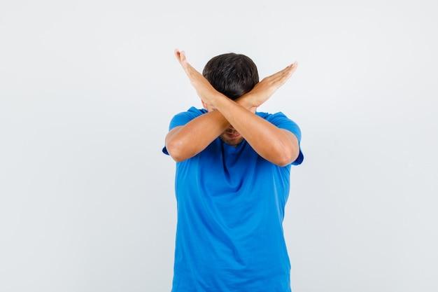 Jonge man stop gebaar in blauw t-shirt tonen en uitgeput op zoek.