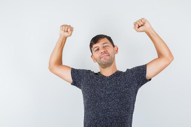 Jonge man strekt zijn armen uit in een zwart t-shirt en ziet er flexibel uit. vooraanzicht.