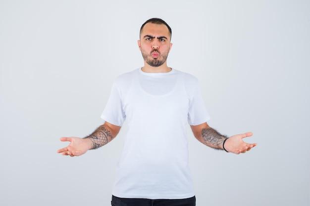 Jonge man strekt zijn handen op vragende wijze uit in een wit t-shirt en een zwarte broek en kijkt perplex