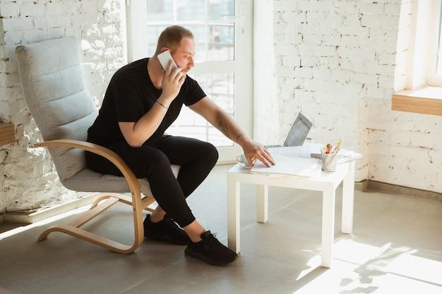 Jonge man studeert thuis tijdens online cursussen voor analytics, financiers, economen. beroep krijgen terwijl geïsoleerd, quarantaine tegen verspreiding van het coronavirus. met behulp van laptop, smartphone, apparaten.