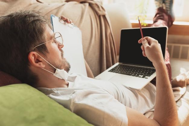 Jonge man studeert thuis tijdens online cursussen voor journalisten, critici, schrijvers. beroep krijgen terwijl geïsoleerd, quarantaine tegen verspreiding van het coronavirus. met behulp van laptop, smartphone, koptelefoon.