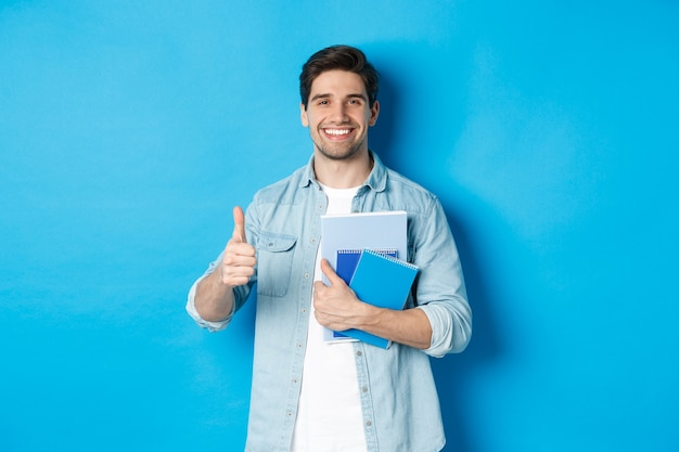 Jonge man student met notitieboekjes, duim omhoog in goedkeuring, glimlachend tevreden, blauwe studio achtergrond