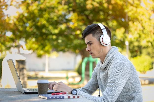 Jonge man studeren met computer terwijl u luistert naar muziek met een koptelefoon in het park zonder masker