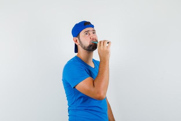 Jonge man tanden poetsen terwijl hij in blauw t-shirt en pet opkijkt en peinzend kijkt