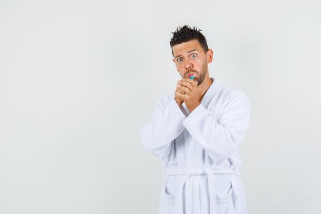 Jonge man tandenpoetsen in witte badjas en op zoek grappig, vooraanzicht.