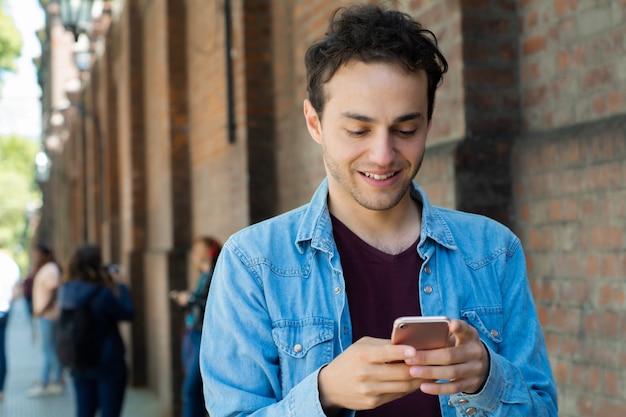 Jonge man te typen op zijn telefoon.