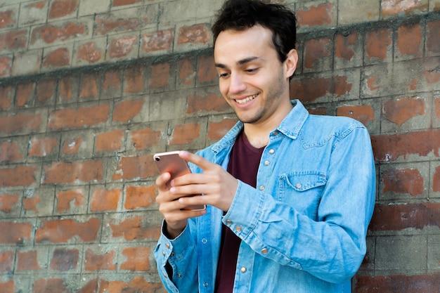 Jonge man te typen op zijn telefoon