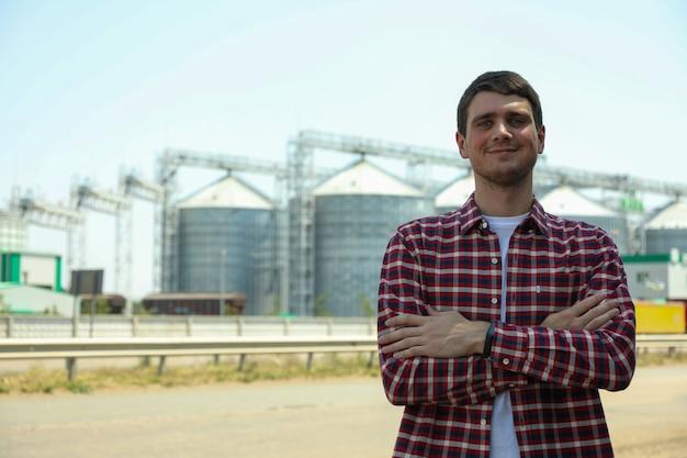 Jonge man tegen graansilo's. landbouwbedrijf