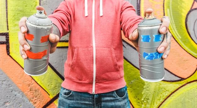 Jonge man tekenen met sprays. graffitikunstenaar het schilderen met de blikken van de aërosolkleur op de muur