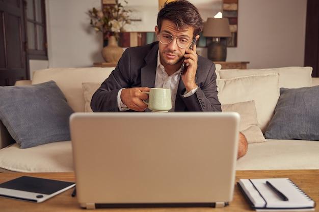 Jonge man telewerken vanuit huis in videoconferentie, zittend op de bank in een pak en korte broek. drink koffie en praat via de mobiele telefoon.