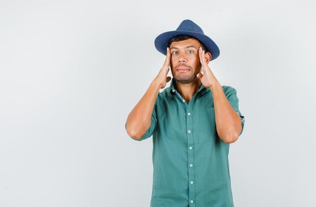 Jonge man tempels aan te raken met vingers in shirt, hoed en neergeslagen kijken.