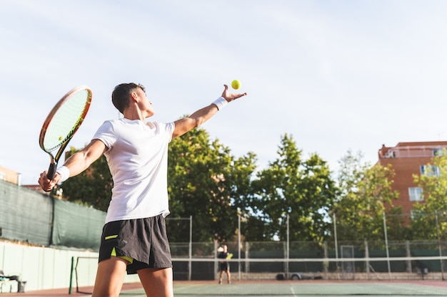 Jonge man tennissen buitenshuis.