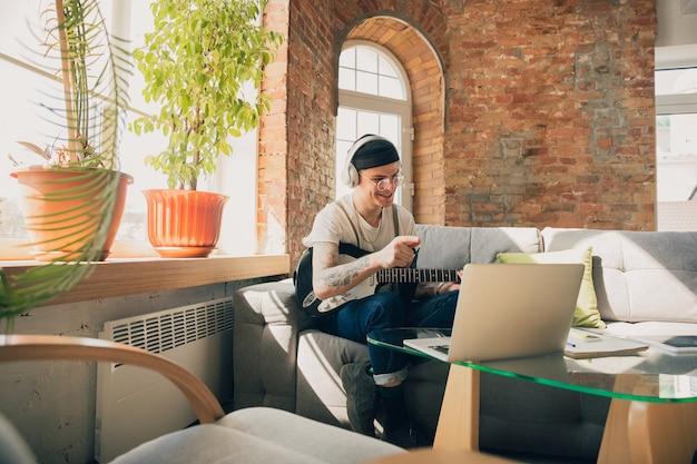 Jonge man thuis studeren tijdens online cursussen of gratis informatie zelf