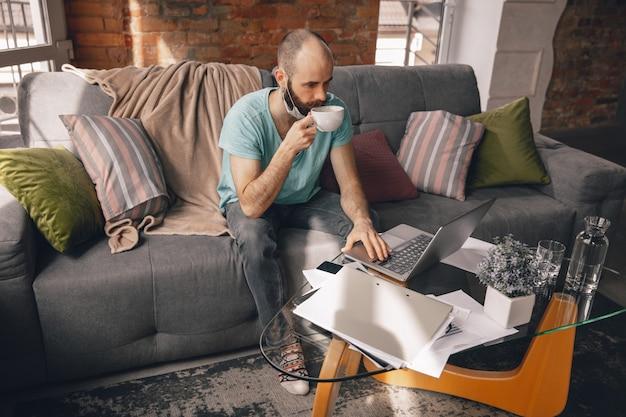 Jonge man thuis tijdens quarantaine en freelancers