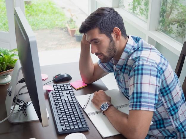 Jonge man thuis werken en benadrukt over de baan