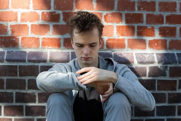 Jonge man, tiener zit door een bakstenen muur en kijkt op zijn horloge