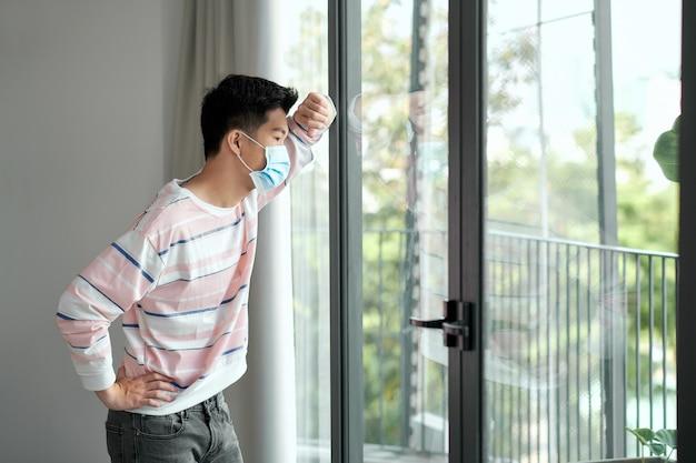 Jonge man tijdens een pandemie van het coronavirus die thuis een gezichtsmasker draagt voor sociale afstand