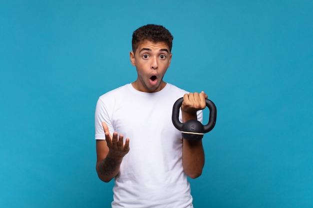 Jonge man tilde een sumbbell met open mond en verbaasd, geschokt en verbaasd met een ongelooflijke verrassing