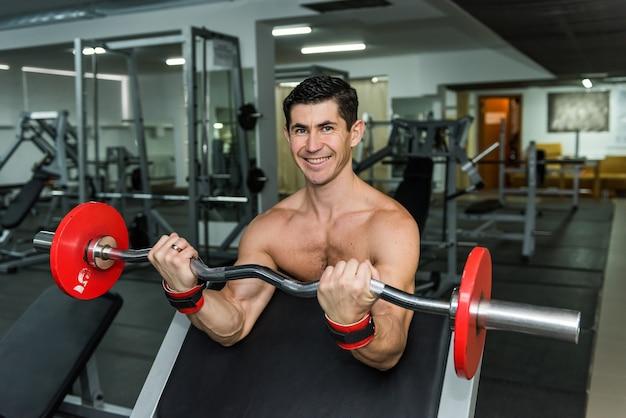 Jonge man tillen barbell in sportschool