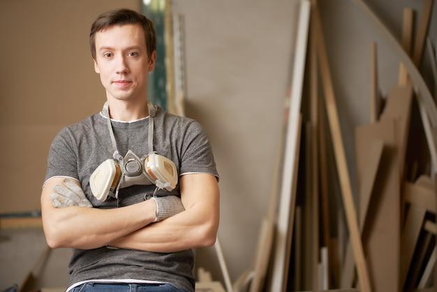 Jonge man timmerman met gekruiste armen in werkplaats