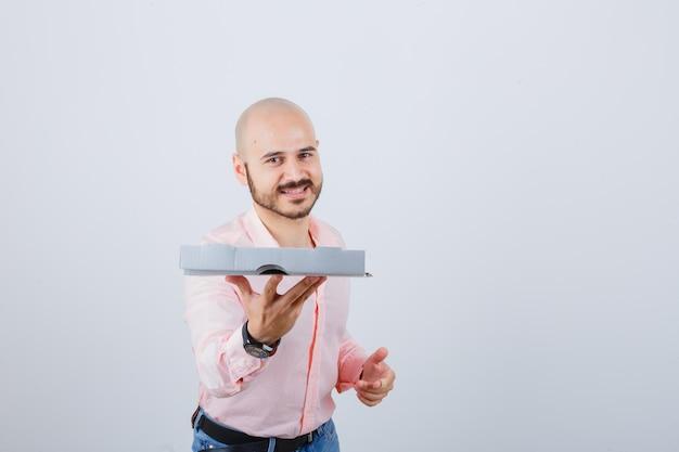Jonge man toont gebaar in shirt, spijkerbroek en ziet er optimistisch uit. vooraanzicht.