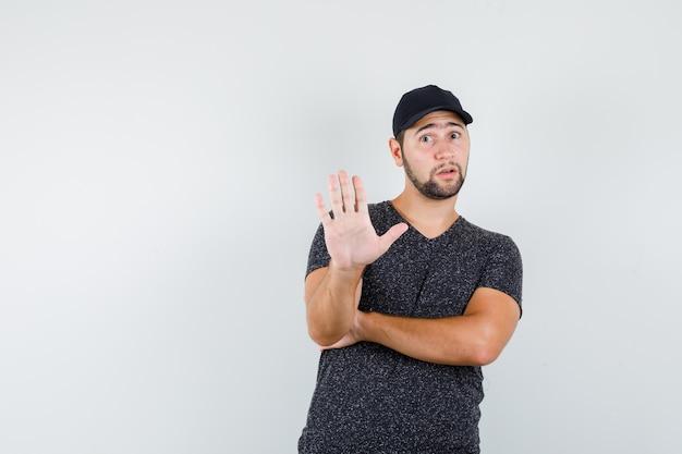 Jonge man toont geen gebaar in t-shirt en pet en kijkt bang