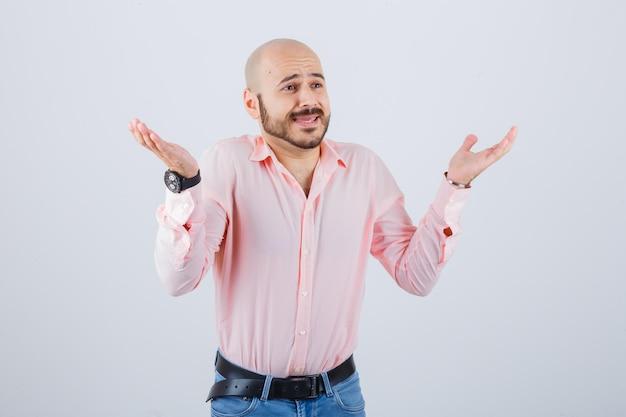 Jonge man toont hulpeloos gebaar in shirt, spijkerbroek en kijkt bezorgd. vooraanzicht.