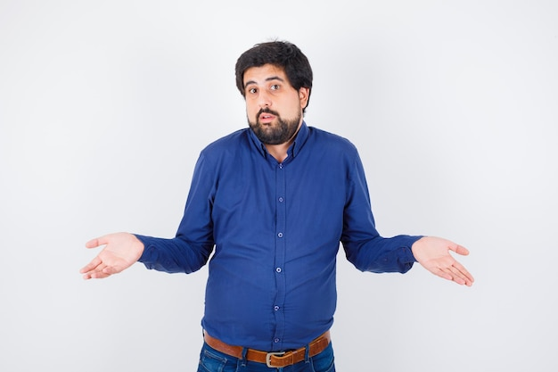 Jonge man toont hulpeloos gebaar in shirt, spijkerbroek en ziet er verward uit.