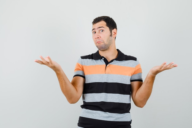 Jonge man toont hulpeloos gebaar in t-shirt en kijkt verbaasd, vooraanzicht.