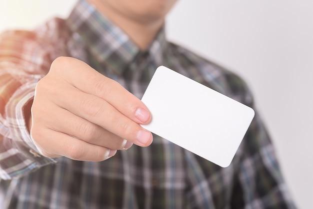 Jonge man toont, leeg adreskaartje uit de zak van zijn overhemd voor mock up design templet