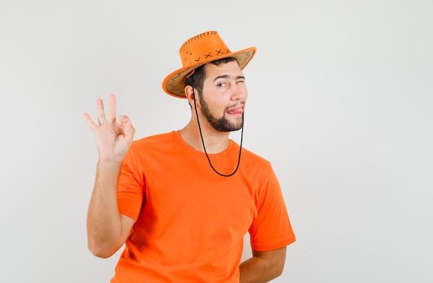 Jonge man toont ok gebaar, tong uitsteekt, knipogend oog in oranje t-shirt, hoed, vooraanzicht.