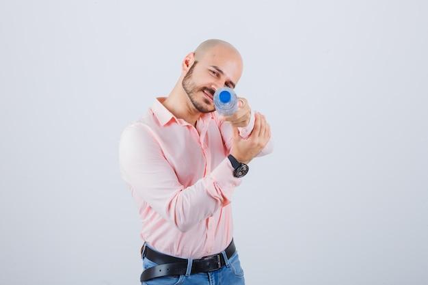 Jonge man toont pistoolgebaar met waterfles in shirt, spijkerbroek en ziet er grappig uit. vooraanzicht.