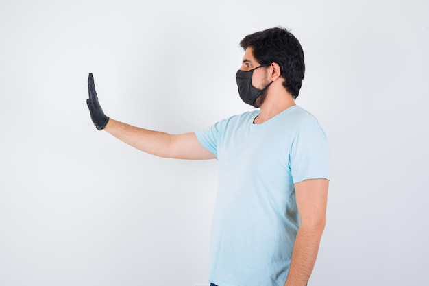 Jonge man toont stopgebaar in t-shirt en ziet er zelfverzekerd uit, vooraanzicht.