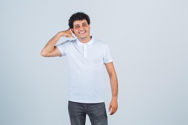 Jonge man toont telefoongebaar in wit t-shirt, broek en ziet er vrolijk uit, vooraanzicht.