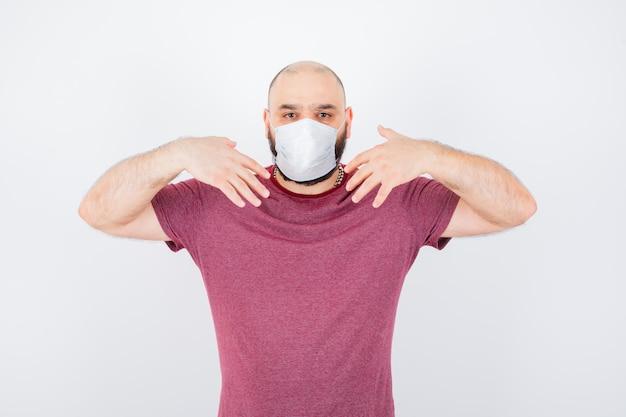 Jonge man toont zichzelf in roze t-shirt, masker vooraanzicht.