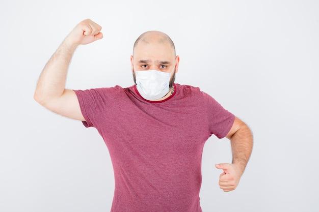 Jonge man toont zijn armspieren in roze t-shirt, masker en ziet er krachtig uit, vooraanzicht.