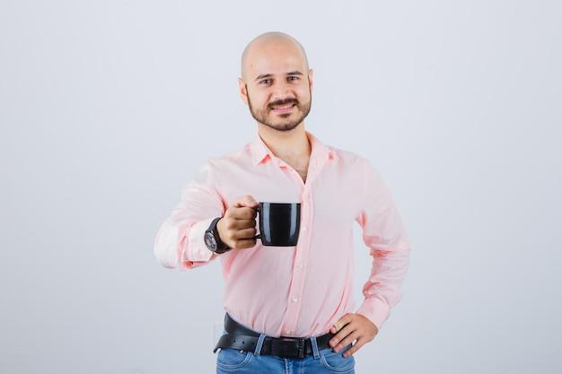 Jonge man toont zijn kopje thee in roze shirt, spijkerbroek en ziet er tevreden uit. vooraanzicht.
