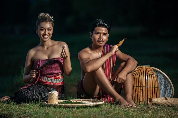 Jonge man topless met lendenen in landelijke levensstijl en jonge mooie vrouw, boerenpaar heeft diner