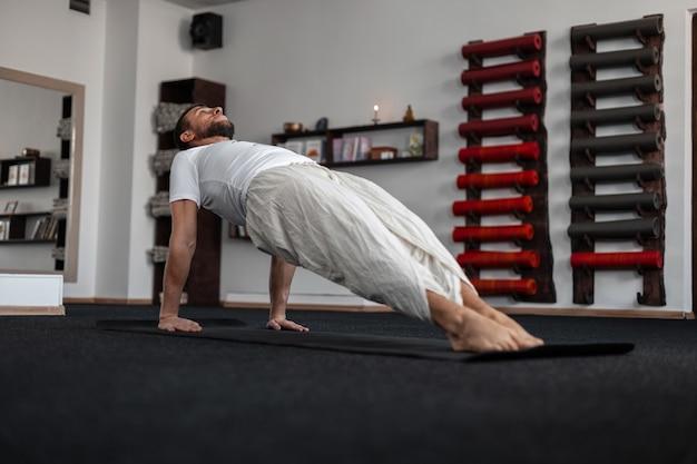Jonge man trainer beoefenen van yoga in de fitnessruimte. guy is aan het uitrekken. gezond levensstijlconcept.