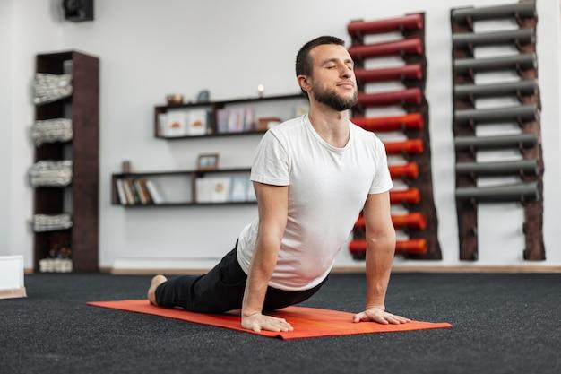 Jonge man trainer doet yoga oefening in de sportschool.