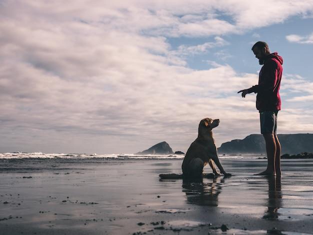 Jonge man training met zijn hond op het strand