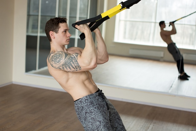 Jonge man training oefening push-ups met trx fitness riemen in de sportschool