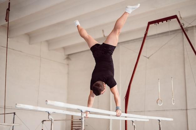 Jonge man training op parallelle staven