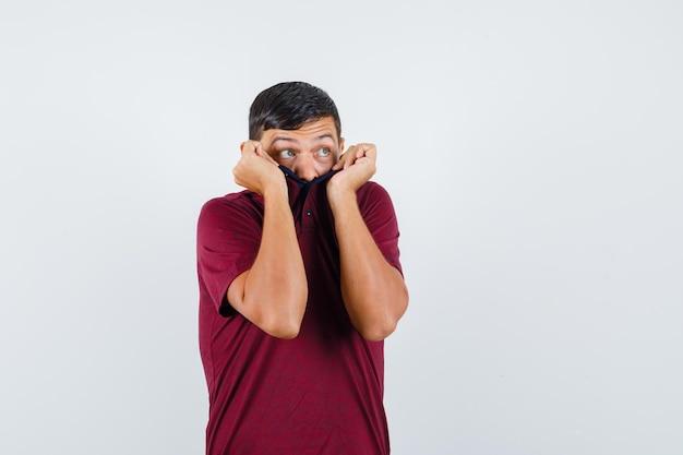 Jonge man trekt kraag op gezicht in t-shirt en ziet er bang uit, vooraanzicht.