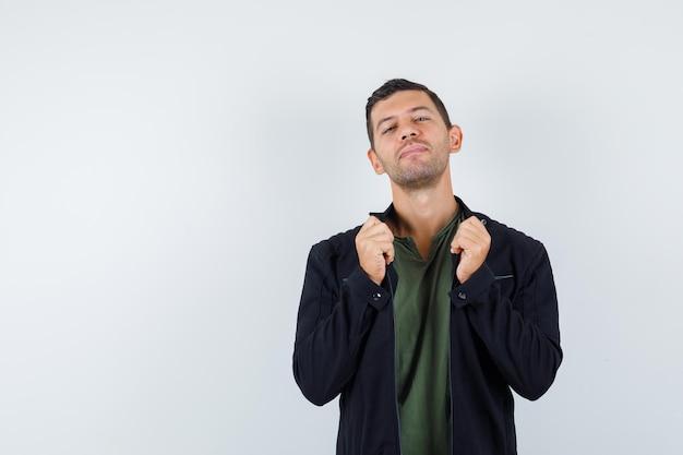 Jonge man trekt kraag van zijn jas in t-shirt, jas en ziet er cool uit. vooraanzicht.